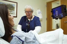 A patient and nurse use a mobile device to connect with a video remote medical interpreter