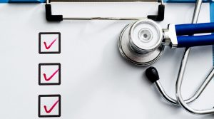 A checklist on a clipboard with a stethoscope