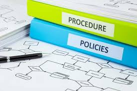 Two binders labeled Procedure and Policies sitting on top of an office organizational chart